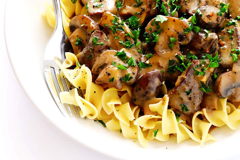 Beef Stroganoff sprinkled with parsley on white plate with fork