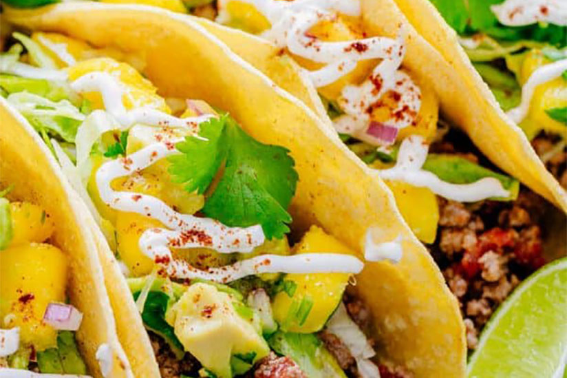 Beef tacos drizzled with mayonnaise with sprinkle of chili powder