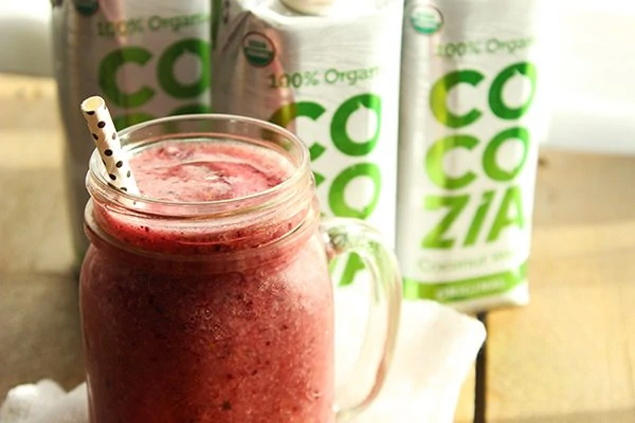 coconut water and fruit smoothie in glass with straw