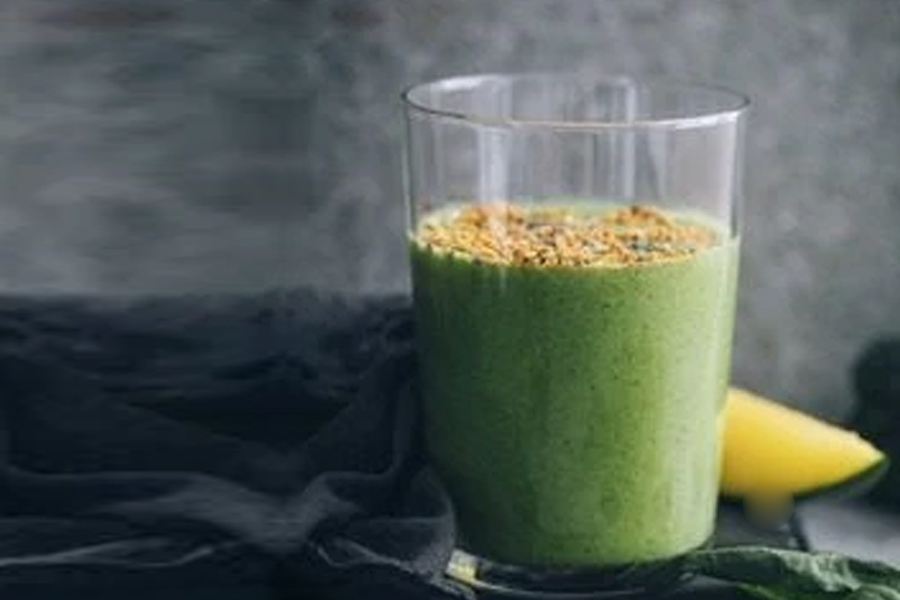 Spinach and mango smoothie in tall glass with bee pollen on top