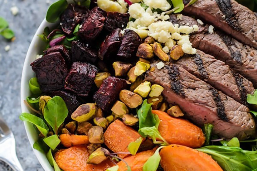 Salad with grilled steak and roasted vegetables in white bowl on counter
