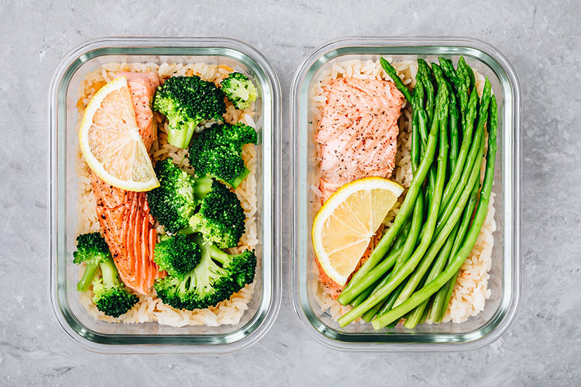 Salmon on rice with asparagus and broccoli in lunch box containers