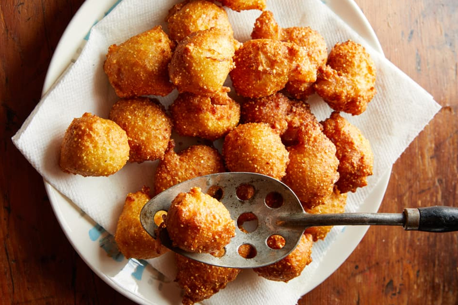 Deep-fried hush puppies on white plate with spoon