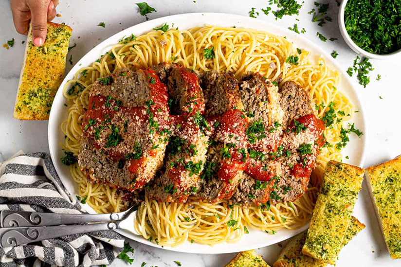 Meatloaf Spaghetti on white dish with side of garlic bread slices on counter