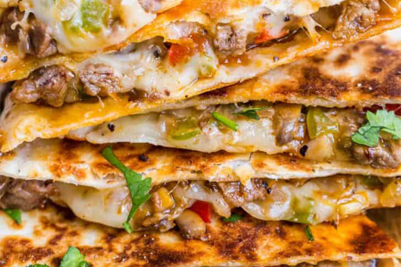 Stacked cheesesteak quesadilla with cheese and diced peppers
