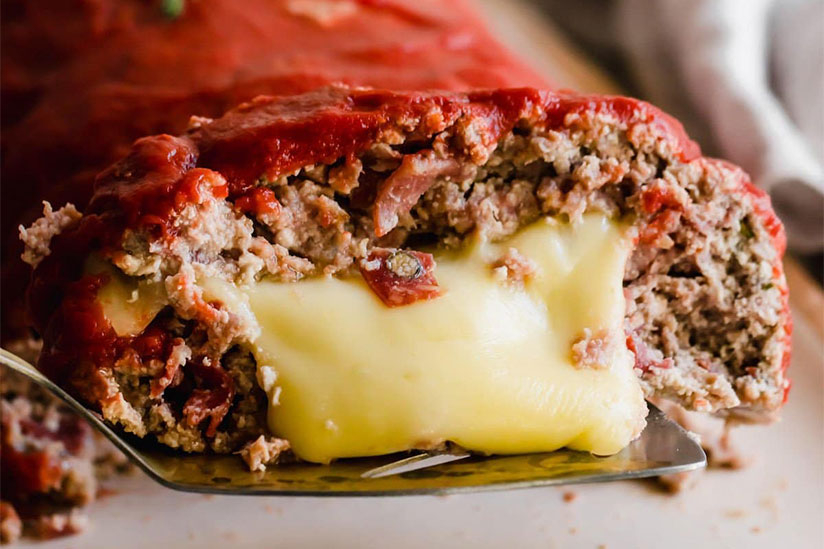 Pizza meatloaf with cheese overflowing on metal spatula