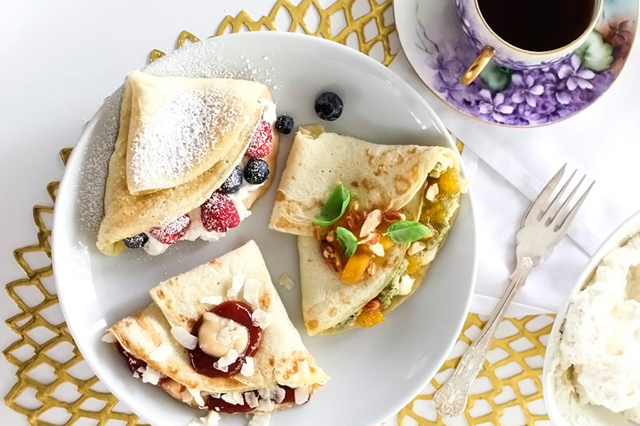 three crepes on white plate on table