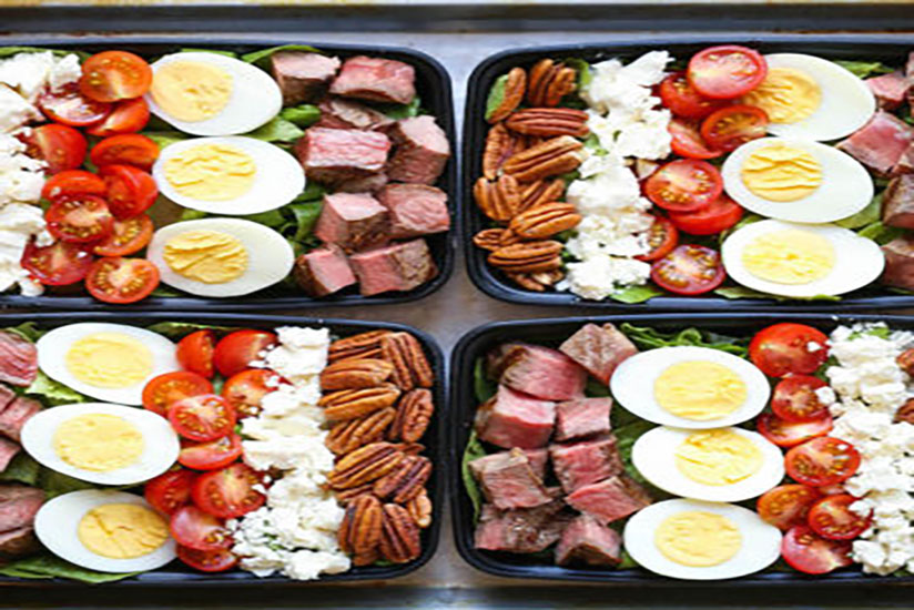 Four steak Cobb salad meals in black to-go boxes on counter