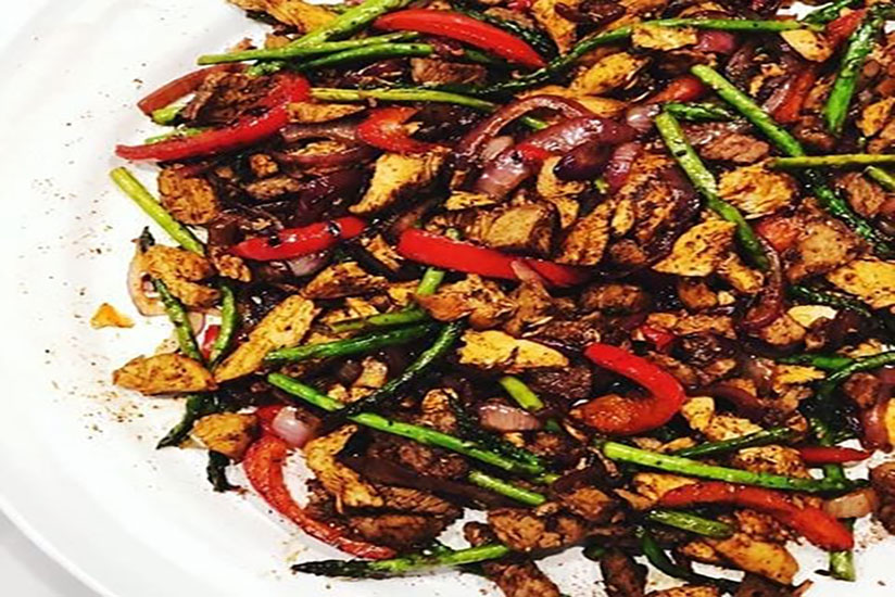 Steak fajitas with sliced asparagus and bell peppers on white plate
