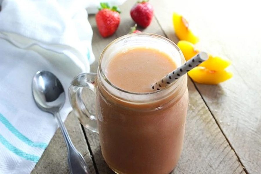 stawberry and banana smoothie in glass with straw