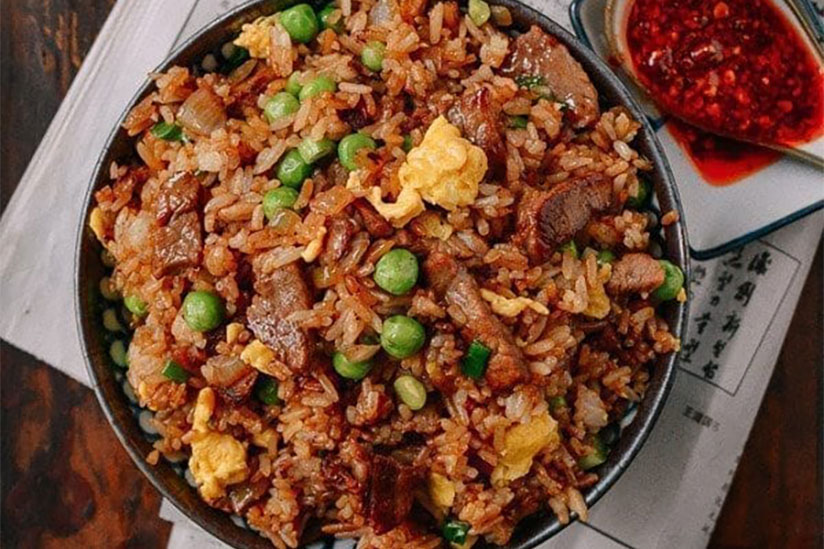 Beef fried rice in black bowl with side of chili sauce on wood counter