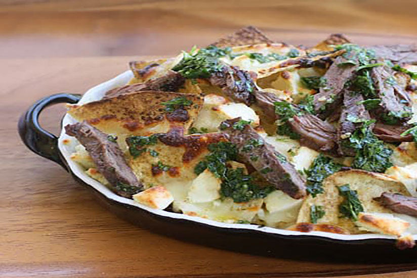 Chimichurri nachos topped with steak slices in black dish on wood counter