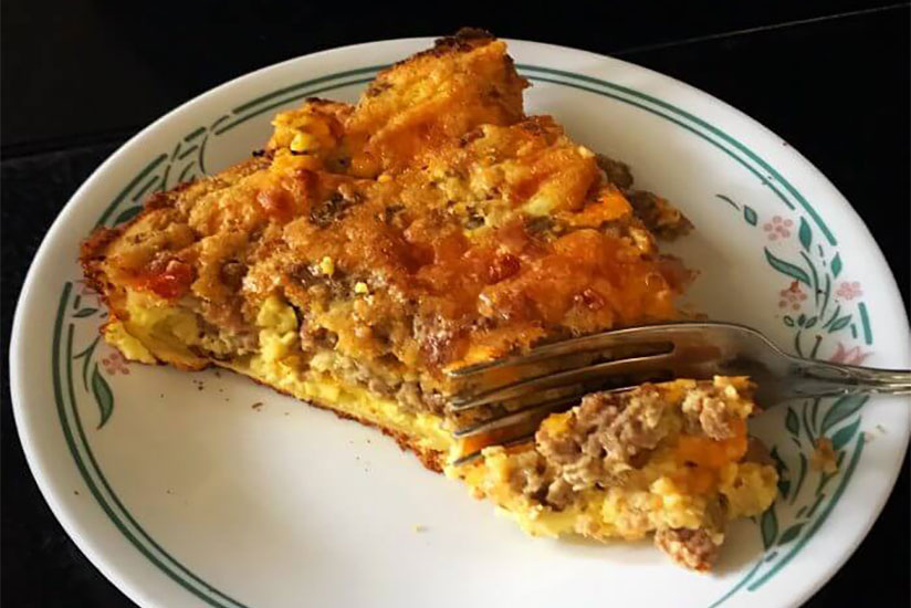 Fork cutting into slice of meatloaf quiche on white plate