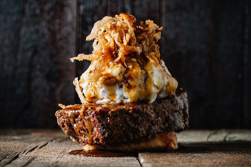 Meatloaf sandwich topped with mashed potato and fried onions with gravy