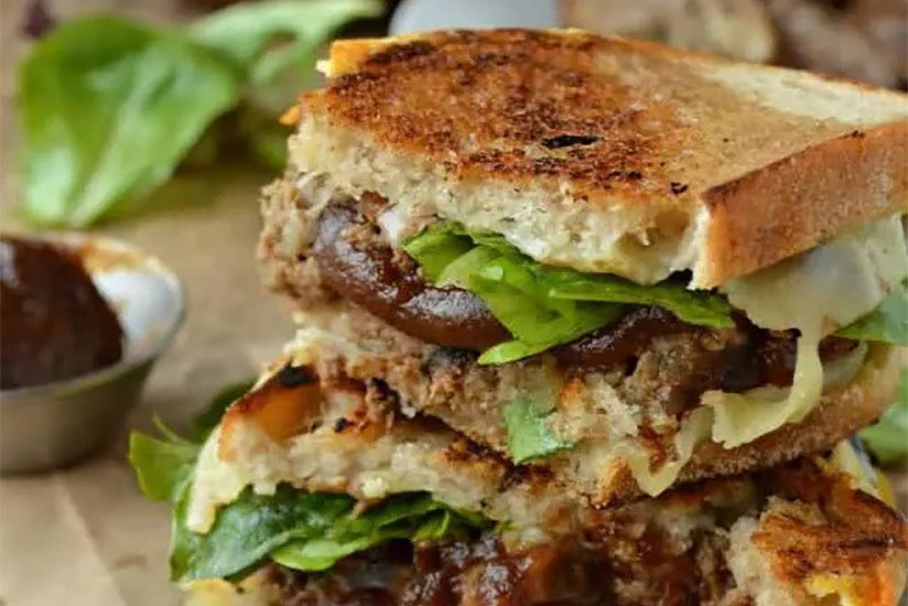 Meatloaf sandwich with toasted bread on wood counter