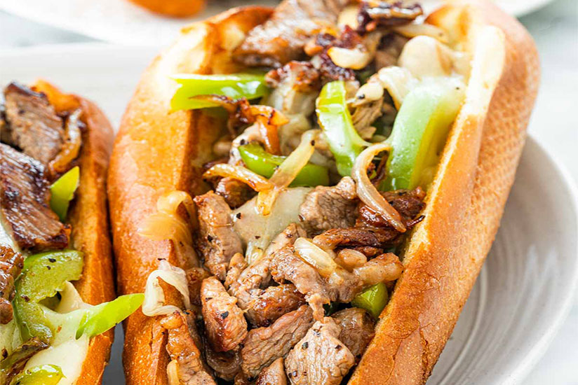 Philly cheesesteak sandwich topped with chopped bell peppers on white plate