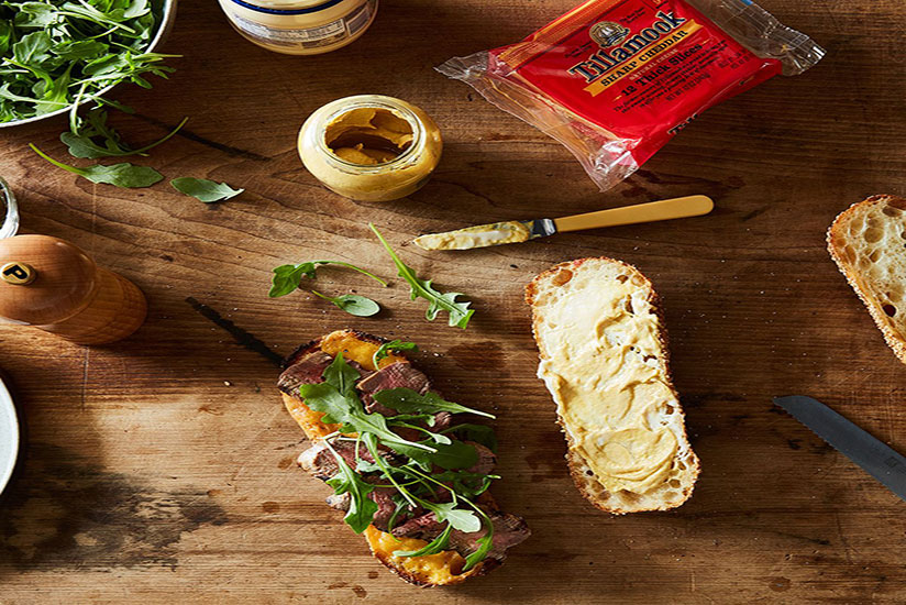 Sliced bread with mustard beside half with steak and arugula on counter