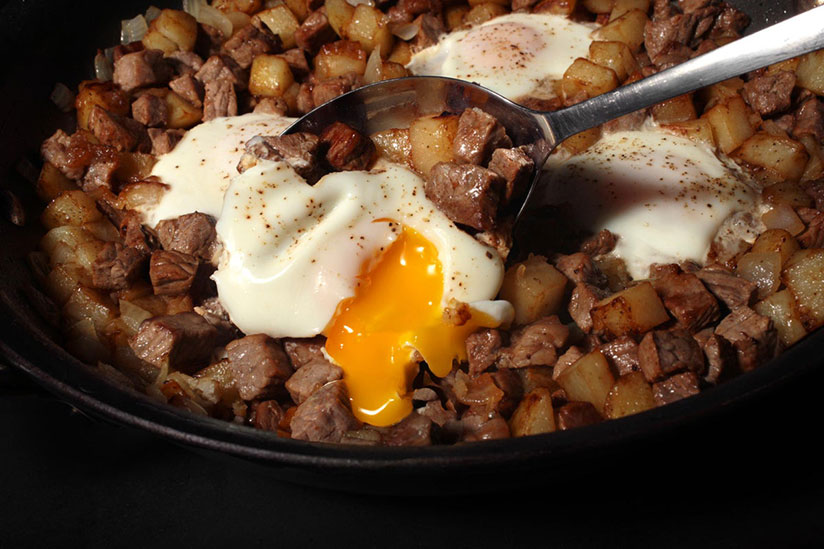 Spoon digging into egg and steak hash in black bowl