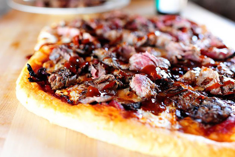 Steak slices on top of pizza dough drizzled with steak sauce on wood counter
