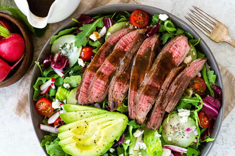 Sliced flank steak on bowl of salad with sliced avocados on white counter