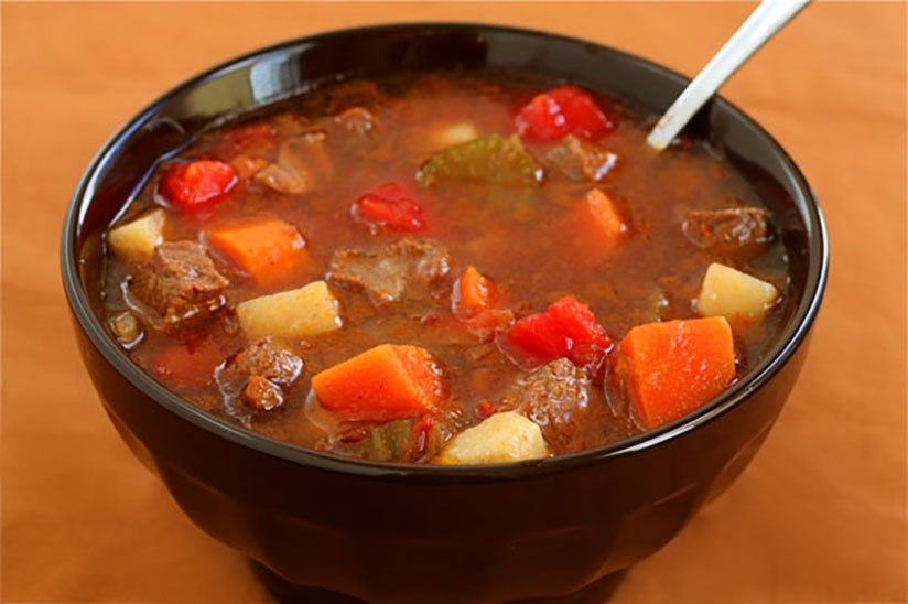 Steak soup with carrots and potatoes in black bowl on wood counter