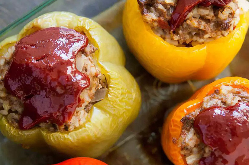 Meatloaf stuffed bell peppers topped with ketchup on brown counter