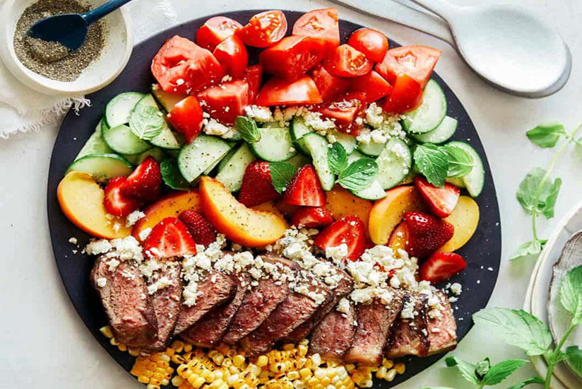 Cold steak salad with sliced peaches, strawberry, and tomatoes on black plate