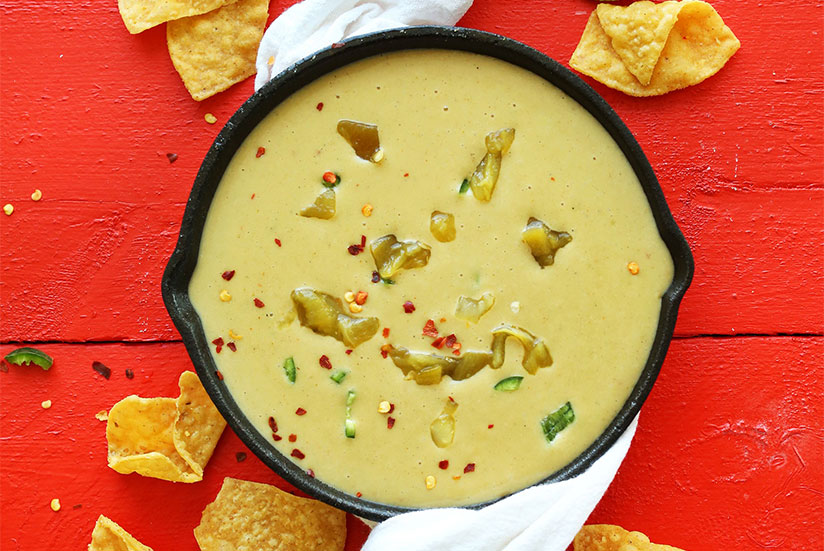 Green chili queso in iron skillet surrounded by limes, chilis, and chips on red wood counter