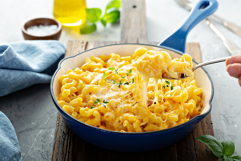 Hand holding spoon scooping baked mac and cheese in blue pan