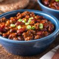 Beef chili con carne topped with green onions in blue bowl on wood counter