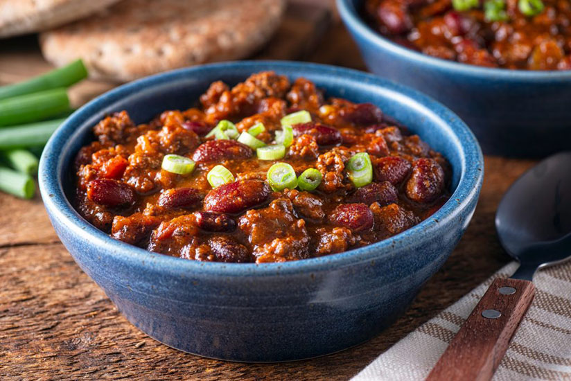 Beef chili con carne in blue bowl on wood counter