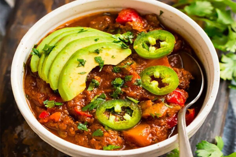 Whole 30 chili with sliced avocados and jalapenos in bowl