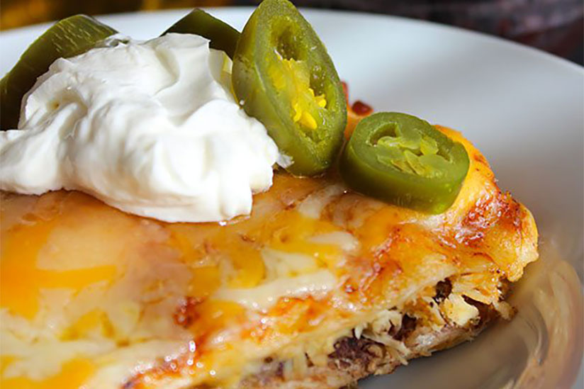 Chicken enchilada topped with sliced jalapenos and sour cream on plate