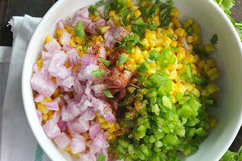 Chipotle corn salad in white bowl on wood counter