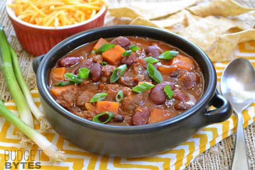 Chorizo sweet potato chili topped with sliced green onions in black pot
