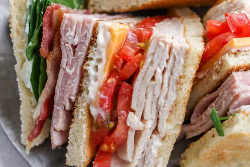 Club sandwich with layers of tomatoes, lettuce, ham, and bacon on plate