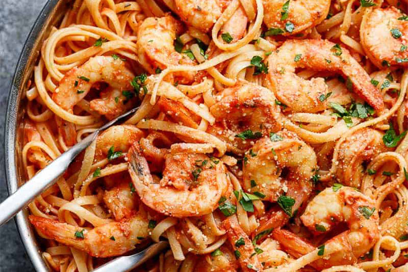 Tomato and shrimp pasta with tongs in pan on marble counter