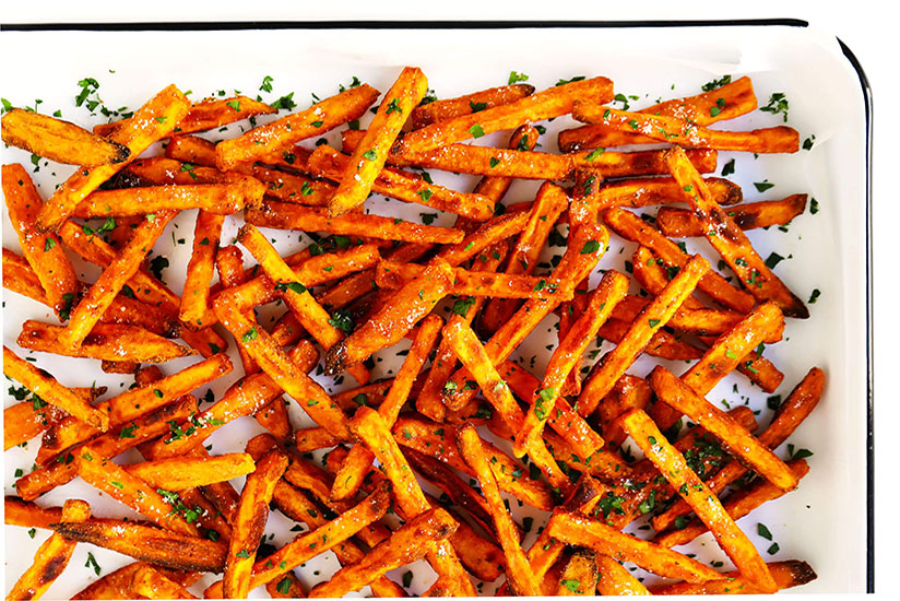Crispy sweet potato fries in clear dish on white background