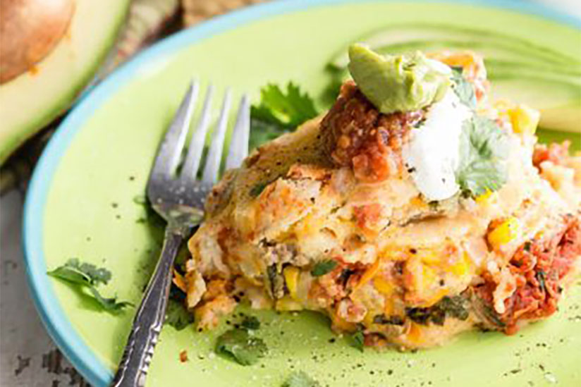 Slow cooked Mexican lasagna topped with avocado on blue and green plate