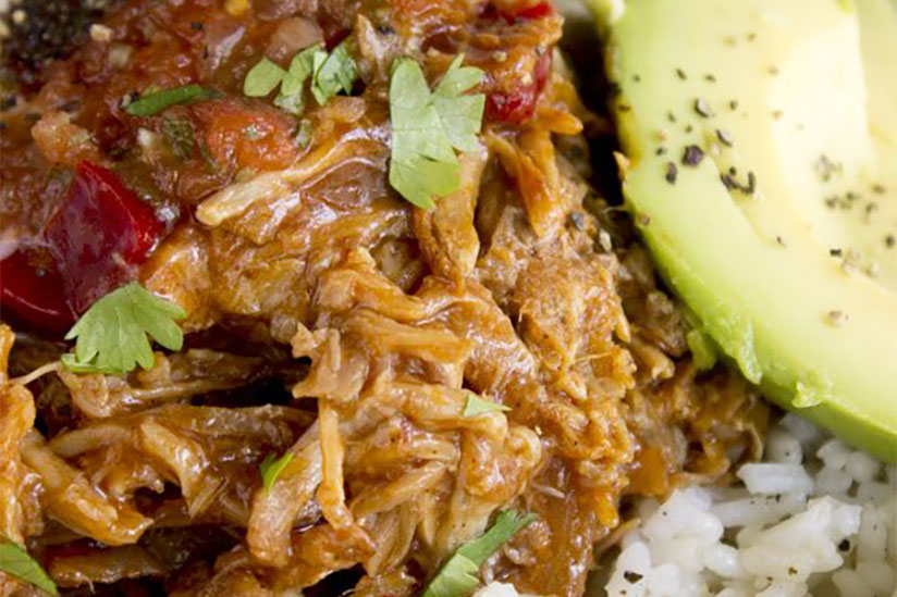 Crockpot pulled pork in bowl of rice with sliced avocados