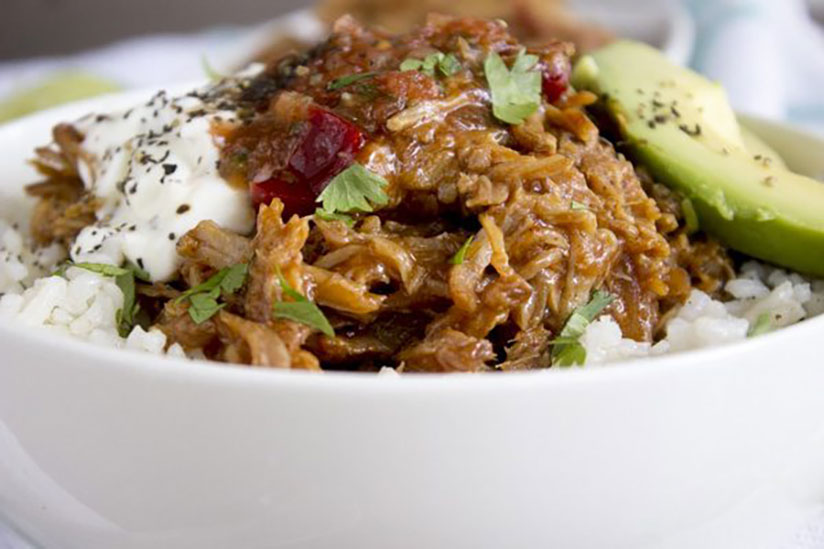 Pulled pork bourbon in bowl of rice with sour cream and sliced avocado