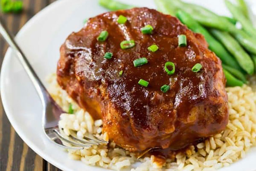 Slow cooked BBQ pork chop on top of rice with steamed vegetables on plate