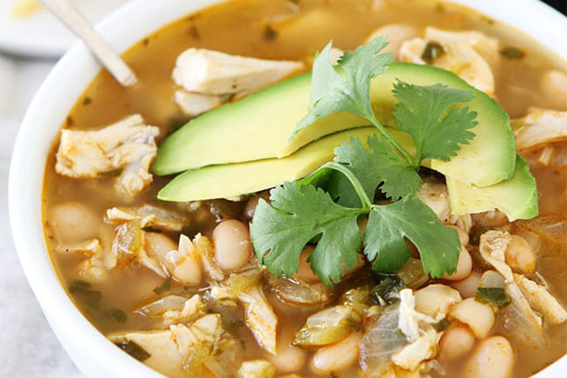 White chicken chili garnished with sliced avocados and cilantro in bowl