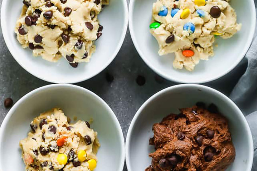 Four white bowls with edible cookie dough in different flavors on marble counter