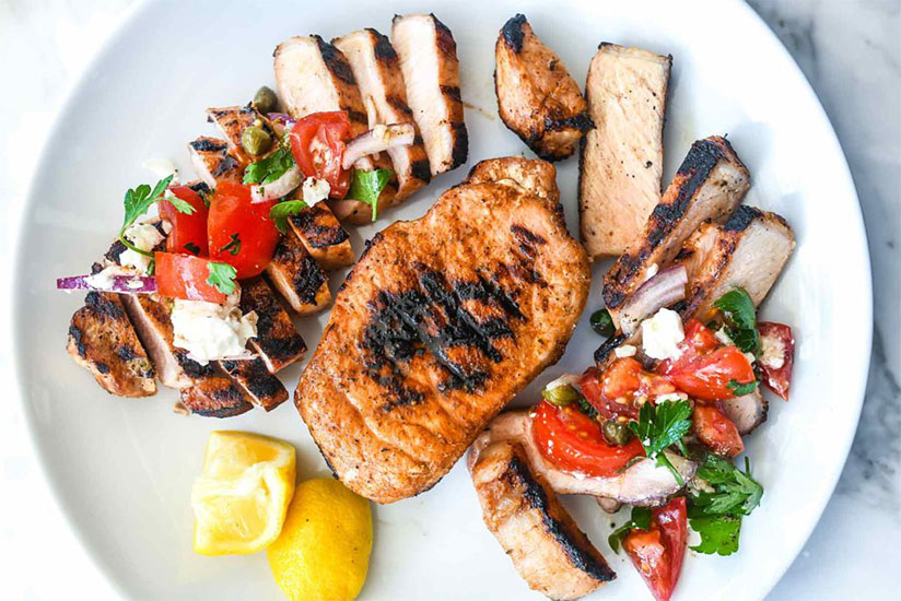 Grilled pork chops topped with tomato salad on white plate