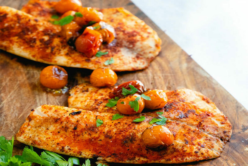 Grilled Tilapia topped with tomatoes and herbs on wood tray