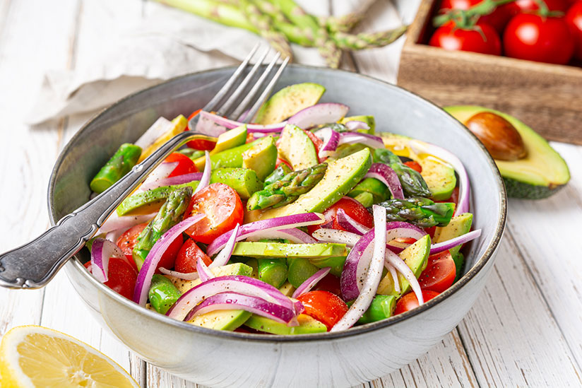 Summer salad sprinkled with pepper in grey bowl with fork on wood counter