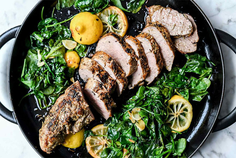 Sliced pork tenderloin with lemon slices and spinach in pan on counter