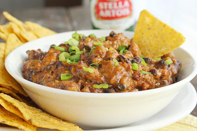 Homemade chili cheese dip with tortilla chip in white bowl