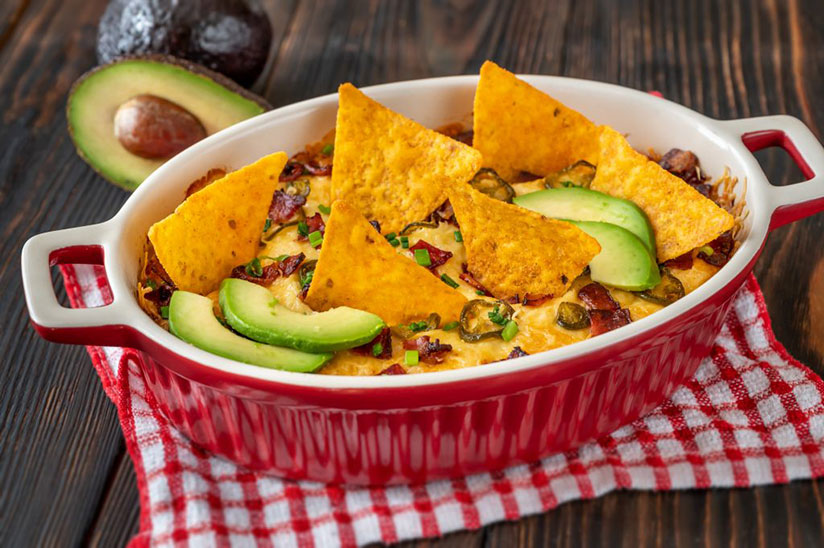 Jalapeno cheese dip in red casserole dish with nachos and avocado slices
